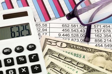 compromisos: Una calculadora y billetes de d�lares tirado en una estad�stica Foto de archivo