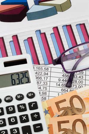obligaciones: Una calculadora y billetes en euros se encuentran en una estad�stica