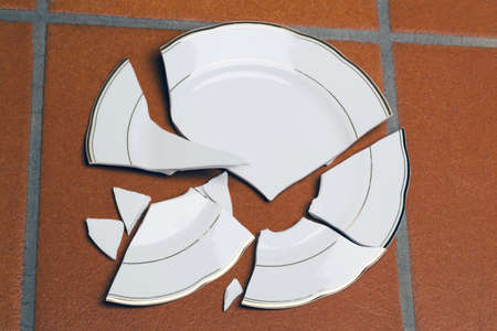 smash: A broken plate lying on a floor. Symbolic photo for divorce and separation.