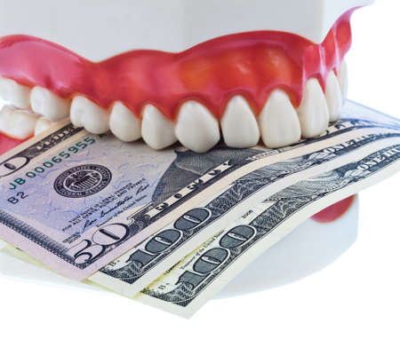 surgery expenses: A dental model to the dentist with dollar bills. Cost of Health. Stock Photo