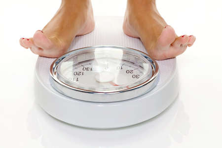 thinness: The feet of a woman standing on scales