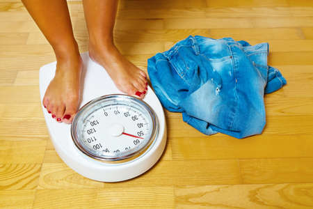 lose weight: The feet of a woman standing on scales