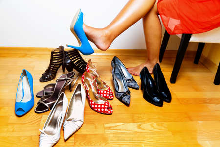 A young woman has many different shoes to choose from Stock Photo - 10537770