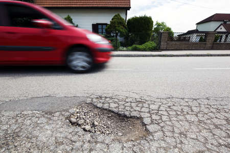 pothole: A road with potholes after the winter frost upheavals. Stock Photo