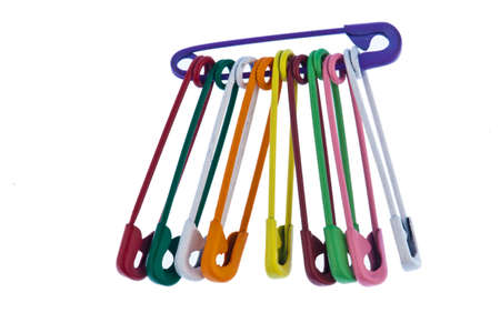 Lots of colorful safety pin lying on a white background photo