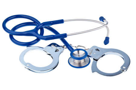 bribes: Handcuffs and a stethoscope lying on a white background. Stock Photo