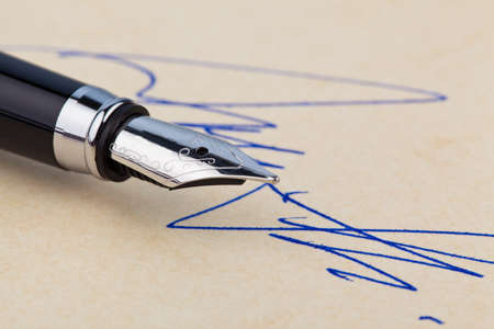 autograph: a fountain pen and a signature on yellow paper. symbolic of closing deals. Stock Photo