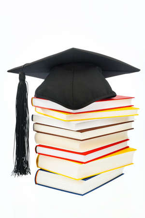 mortarboard: a mortarboard on a book stack on white background. icon image for costs in training and education
