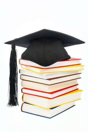 ein Hut auf einem Buch Stack auf wei�em Hintergrund. Symbolbild f�r Kosten in aus- und Weiterbildung Lizenzfreie Bilder