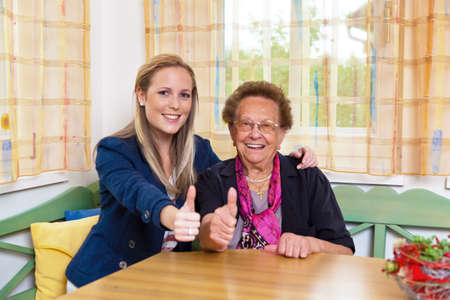 consent: a grandchild visiting his grandmother. laughter and joy. thumbs up Stock Photo