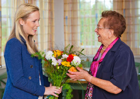 a grandchild visiting his grandmother and bring flowers as a gift. photo