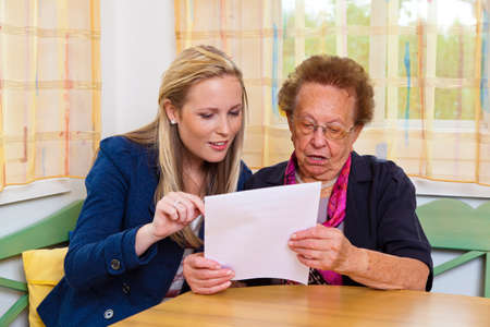 the inheritance: a grandchild visiting his grandmother, and read a contract Stock Photo