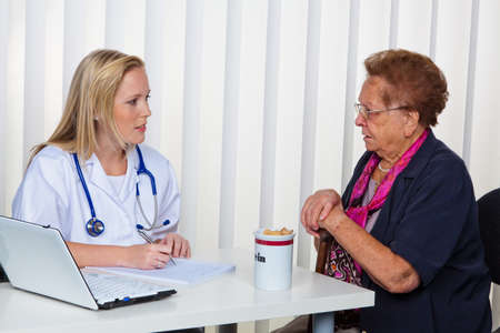 physican: an elderly lady at the doctor in practice. consultation with the doctor.