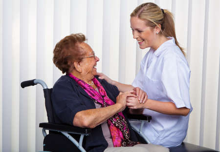 social work: a nurse and an old woman in a wheelchair. Stock Photo