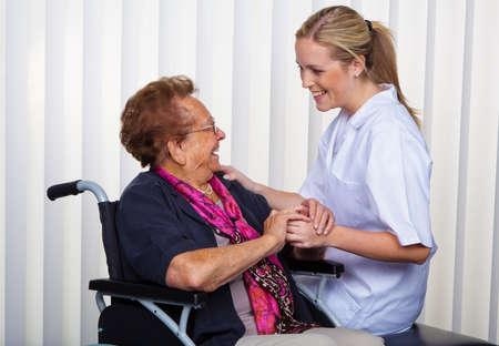 trabajo social: una enfermera y una anciana en silla de ruedas.