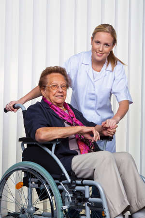 citizens: a nurse and an old woman in a wheelchair. Stock Photo