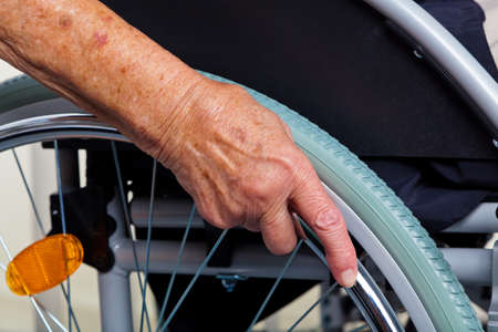 difficulties: a nurse and an old woman in a wheelchair. Stock Photo
