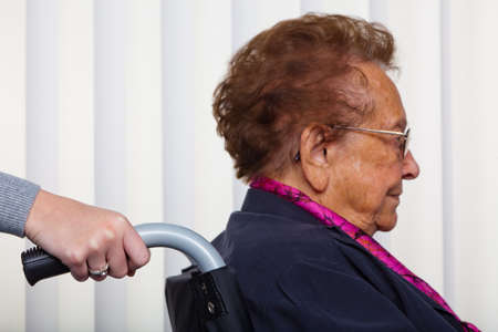 health care worker: a nurse and an old woman in a wheelchair. Stock Photo