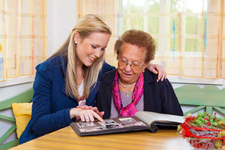 alzheimer: a grandchild visiting his grandmother. view the photo album. Stock Photo