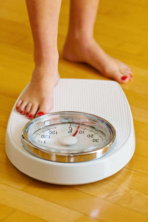 weighing scale: the feet of a woman standing on bathroom scales to turn
