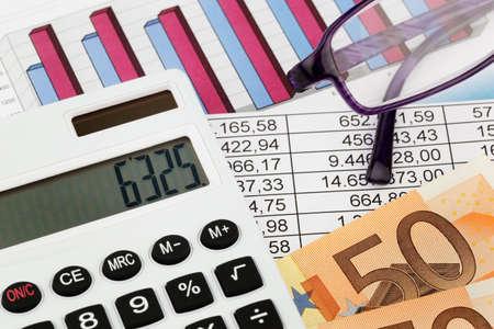 retour: een rekenmachine en diverse statistieken bij de berekening van de balans, de omzet en winst. Stockfoto