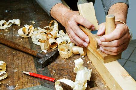 muebles de madera: un carpintero con un cepillo y virutas de madera en el taller.