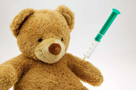 physican: s teddy bear getting an injection. vaccination and syringe.