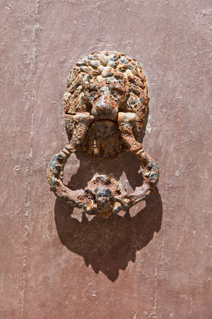 a door knocker on an old door in andalusia, spain. Stock Photo - 10975895