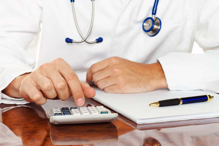 pay bills: doctor with a calculator. calculation of costs and revenues in physician practice and hospital