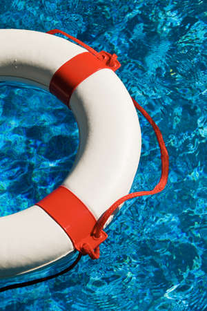indebtedness: a white life ring with red stripes in the blue water.