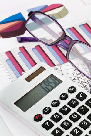 a calculator with graphics of a balance sheet. sales, profit and operating costs. Stock Photo - 11101044
