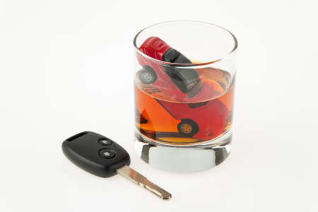 drink and drive: symbol for drunken driving. a car and a carkey in a glass Stock Photo