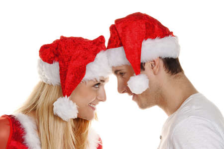 young couple at christmas with santa claus caps photo