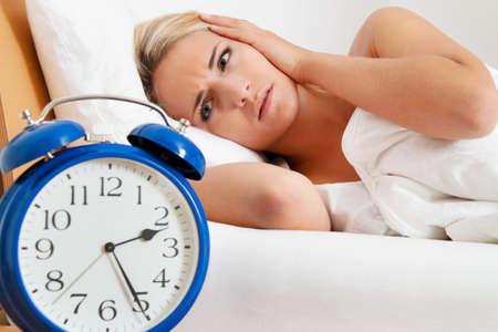 insomnio: reloj con el sueño por la noche. la mujer no puede dormir.