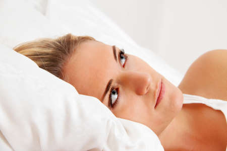a young woman lies awake in bed. sleepless and thoughtful. Stock Photo - 11103845