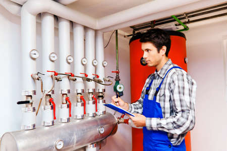 and heating: young engineers in heating boiler heating system with