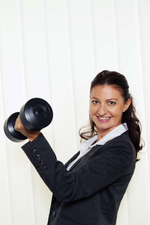 young and successful entrepreneur in the office. holding a dumbbell Stock Photo - 11103853