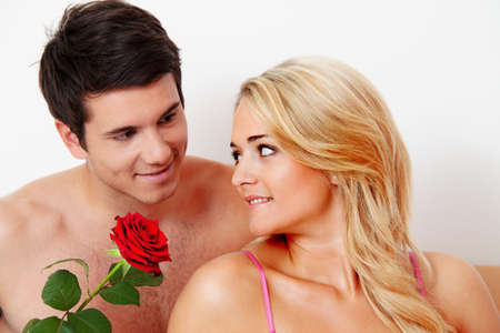 beloved: a romantic couple in bed with rose. marry the man. Stock Photo