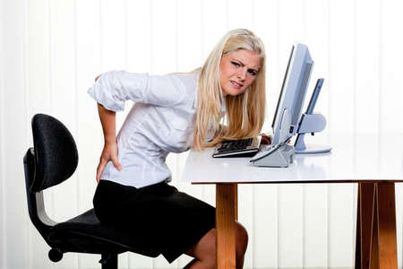 tenseness: young woman with pain in the back office. Stock Photo