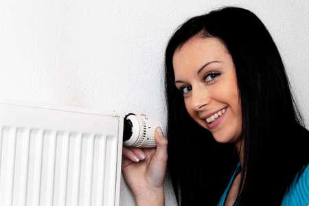 radiador: mujer con un radiador de calefacción y termostato