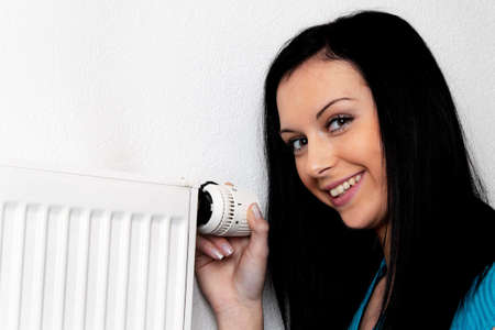 radiator: woman with a heating radiator and thermostat Stock Photo