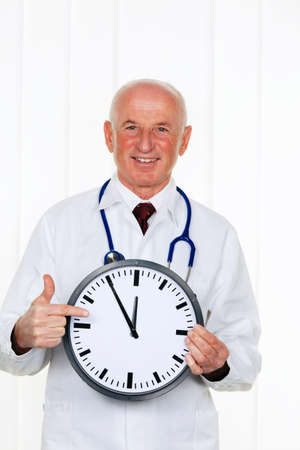 time pressure: a doctor holding a clock. on the ziffernbaltt it is 11:55
