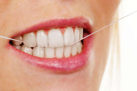 floss: a young woman uses dental floss to clean your teeth