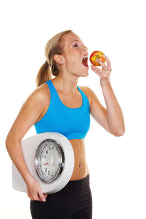 thinness: young woman with bathroom scale and apple. successful diet