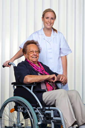 a nurse and an old woman in a wheelchair. photo