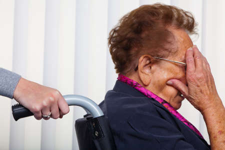 care allowance: a nurse and an old woman in a wheelchair. Stock Photo