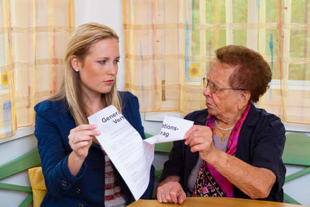 security gap: a grandson visited his grandmother and reads a generational contract. Stock Photo