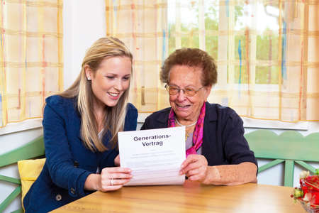 generational: a grandson visited his grandmother and reads a generational contract. Stock Photo