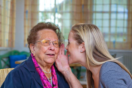 deaf: a grandson to visit his grandmother. listen to the conversation. Stock Photo