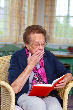 know how: a senior is sitting in an armchair and reading a book
